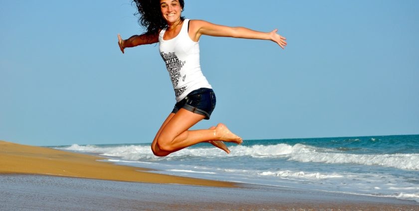 Fit Woman Jumping at Beach